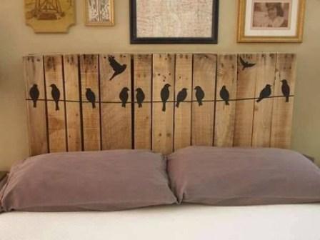Respaldo de cama de palets con pájaros